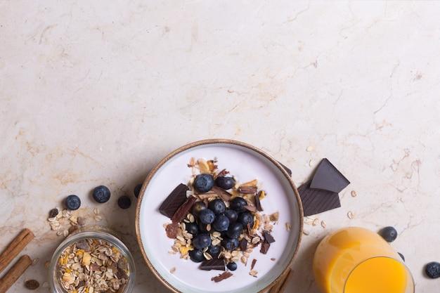 Smoothiekom met yoghurt, verse bessen en ontbijtgranen