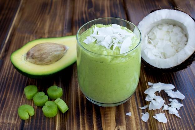 Smoothies met avocado, kokosmelk en selderij op de bruine houten achtergrond