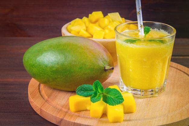 Smoothiesmango met stro en munt in een glasbeker. bord met gesneden mango.