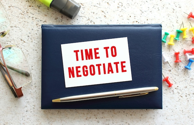 Sms time to negotiate op een visitekaartje dat op een blauw notitieboekje ligt naast de bril en het briefpapier.