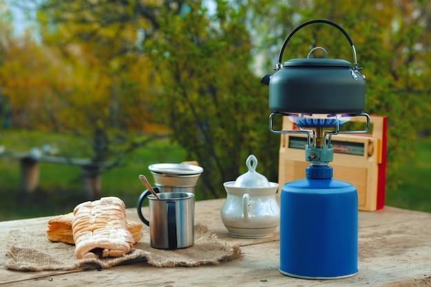 Snack buiten in zomeravond. camping waterkoker, kopjes en koekje op rustieke tafel.
