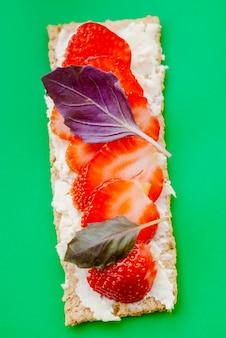 Snack met knäckebröd, roomkaas, aardbei en basilicum op een groene achtergrond