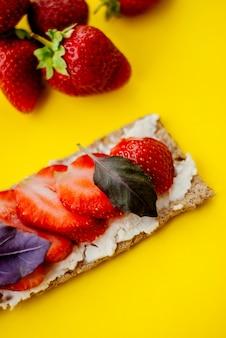 Snack met knäckebröd, roomkaas, verse aardbeien en basilicum op een gele achtergrond