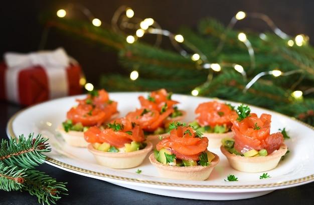 Snack met zalm en avocado op nieuwjaarstafel.