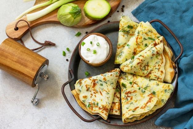 Snack of zomerlunch. courgette pannenkoeken met kruiden geserveerd met zure room in een plaat op een grijze steen of leisteen aanrecht.