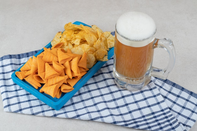 Snack plaat en glas bier op tafellaken