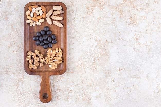 Snack serveren met kleine stapels noten en snoep op een bord