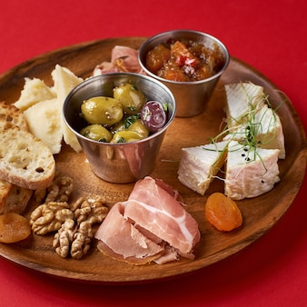Snack set. verscheidenheid aan kaas, olijven, prosciutto, geroosterde stokbroodplakken, selectieve aandacht, vierkant gewas.