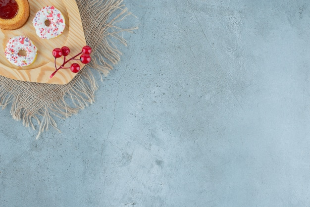 Snack-size donuts en een met gelei gevulde cake op een houten schotel op marmeren achtergrond. hoge kwaliteit foto