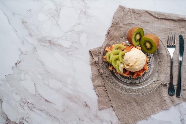Snack van een wafel met ijs, kiwi bovenop op een marmeren achtergrond