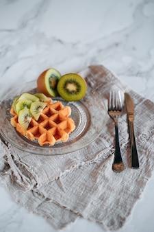 Snack van een wafel met kiwi bovenop op een marmeren achtergrond
