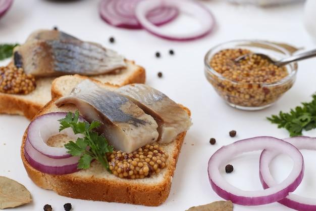 Snack van gezouten haring op brood met rode ui en mosterd op witte achtergrond, horizontaal formaat