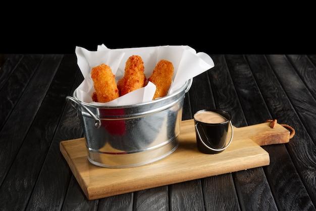 Snack voor bier. gebakken gepaneerde kaas met saus geserveerd in metalen omhulsel