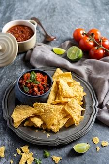 Snack voor een feest, mexicaanse gerechten nachos tortillachips en sipping salsa met tomaat.