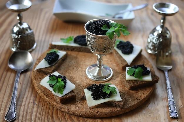 Snack zwarte kaviaar op een houten bruine achtergrond Premium Foto