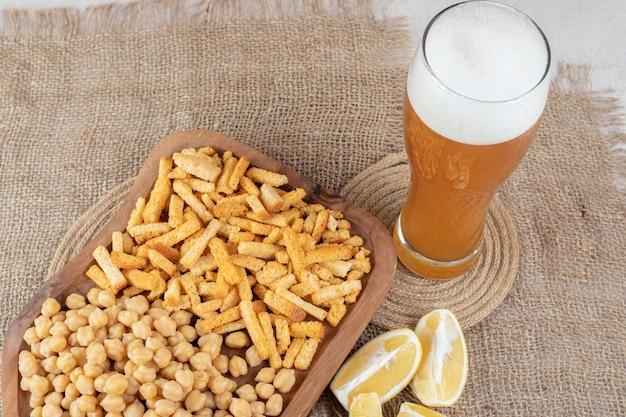 Snackbord, citroen en bier op jute.