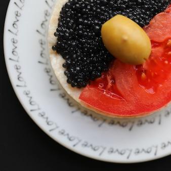 Snackcracker met tomaat, zwarte kaviaar en een olijf.