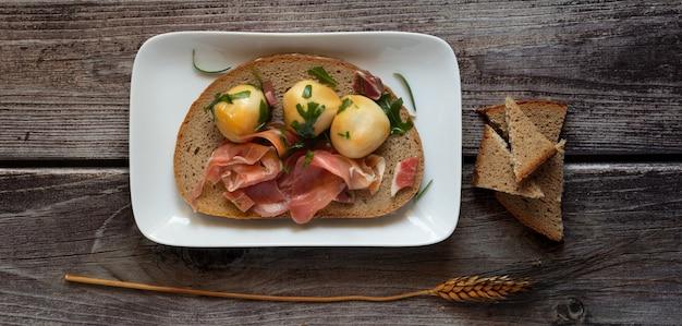 Snackhapje met volkorenbrood, rauwe ham en gerookte provolaballetjes in olie