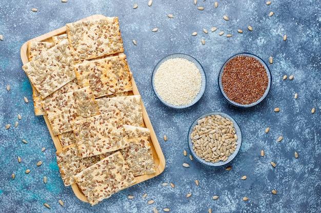 Snackkoekjes met zonnebloempitten, linnenzaad, sesamzaadjes op grijs