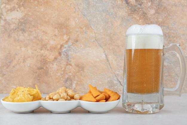 Snackkommen en glas bier op stenen tafel.