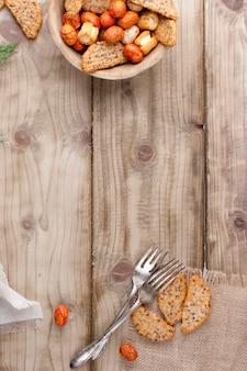 Snacks en beschuit in een beker, vorken, op een houten achtergrond