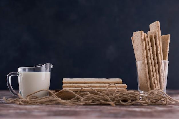 Snacks en crackers in houten schotel met een glas melk op zwarte achtergrond.