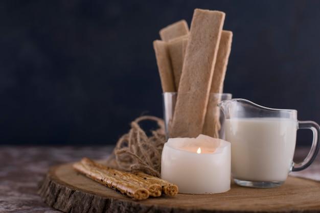 Snacks en crackers met een glas melk op een houten bord.