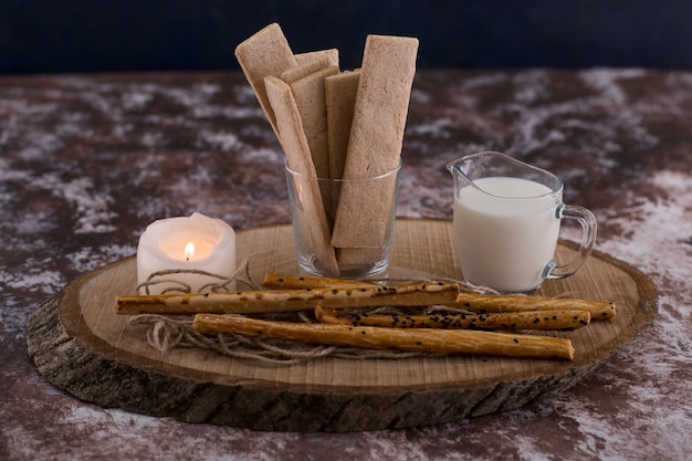 Snacks en crackers met een glas melk op rustiek met een vlammende kaars.