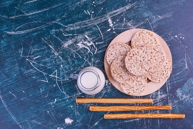 Snacks en crackers op een houten schotel met een potje melk, bovenaanzicht.