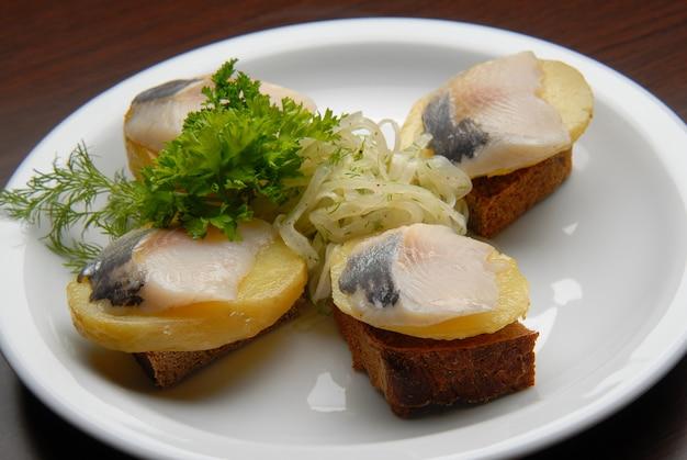 Snacks met zoute vis, aardappelen en uien op brood