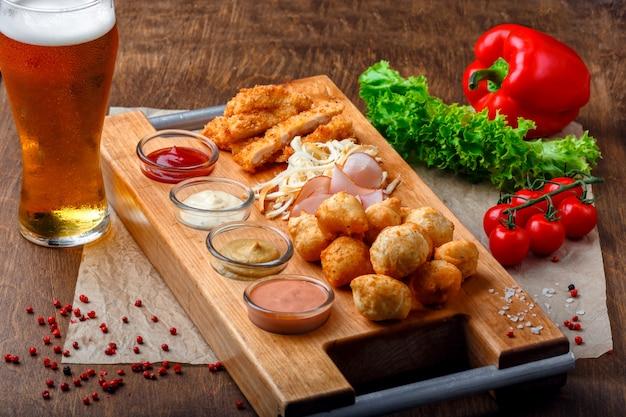 Snacks voor bier, inclusief gefrituurde kaas ballen, varkensstaart kaas, ham en krab sticks op een houten bord