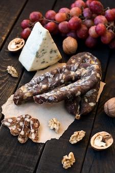 Snacks voor wijn, kaas met schimmel, roze druiven, walnoten en geroosterde droge worst