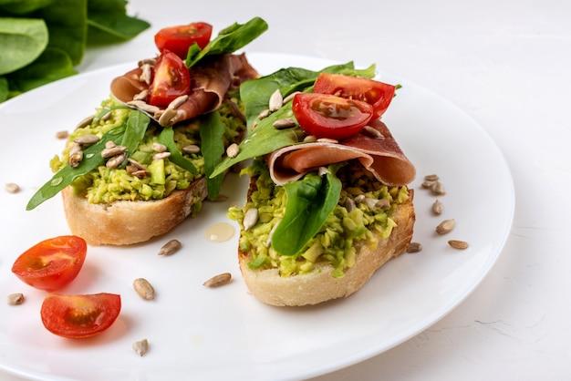 Snacksandwiches met jamon, avocado, tomaten en bladsalade.