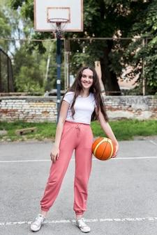 Snak geschoten jong meisje dat een basketbal buiten houdt