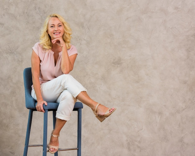Snak geschotene hogere vrouwenzitting op stoel met exemplaarruimte