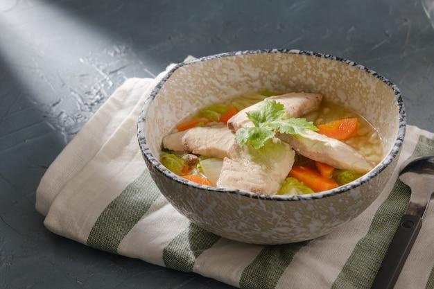 Snakehead vispap gegarneerd met koriander in een kom op grijze tafel. rijstsoep met gesneden vis.