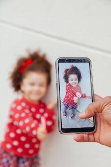 Snap shot van een klein meisje met een smartphone