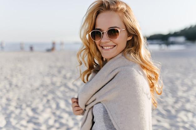 Snapportrait van krullende jonge vrouw in beige outfit en zonnebril glimlachend in het strand