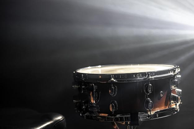 Snaredrum op de achtergrond van een spotlight-percussie-instrument in het donker met podiumrook