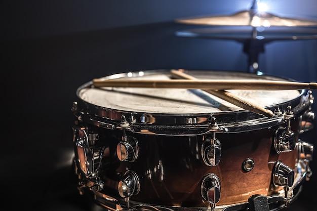 Snaredrum, percussie-instrument op een donkere achtergrond met podiumverlichting.