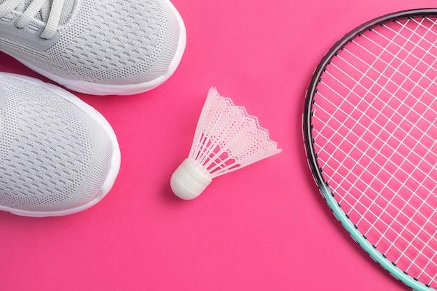 Sneakers, badmintonrackets en shuttle op een felroze.