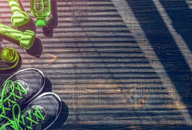 Sneakers dumbbells en een fles water. vlak uitzicht. alles in één kleur.