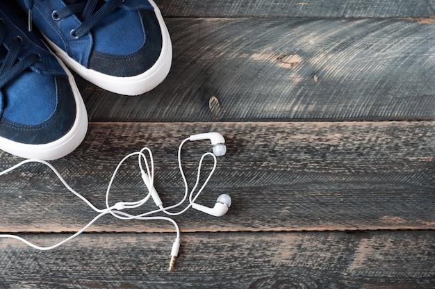 Sneakers en oortelefoons op oude houten achtergrond