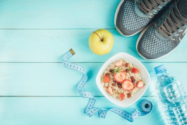 Sneakers, fles water, meetlint, havermout met aardbei en rozijnen en appel op blauw, plat leggen