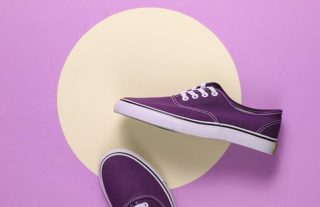 Sneakers in het midden van paarse achtergrond met gele pastel cirkel. jeugd hipster concept. zomerplezier. bovenaanzicht