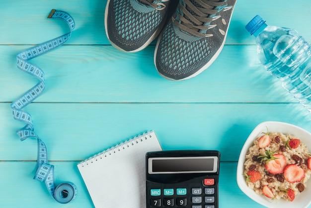 Sneakers, meetlint, notitieboekje, rekenmachine, fles water, appel en havermout met aardbei en rozijnen op blauw, plat leggen