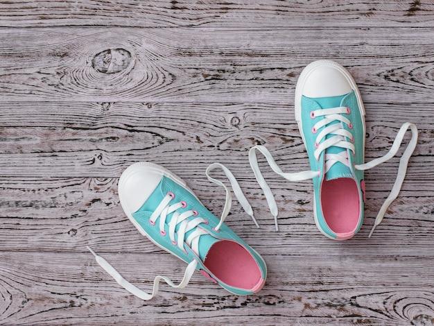 Sneakers met losse veters op de houten vloer.