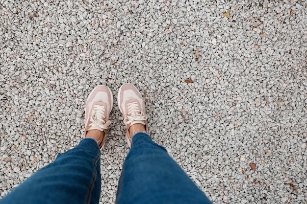 Sneakers staan op de asfalt betonnen vloer. voeten schoenen lopen buiten. hipster van selphie voor jongeren