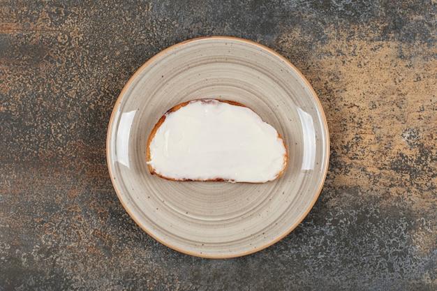 Sneetje toast met zure room op keramische plaat.