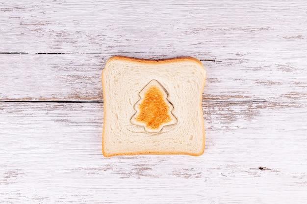 Sneetje toastbrood met geroosterd uitgesneden in de vorm van een spar, kerstvoedsel